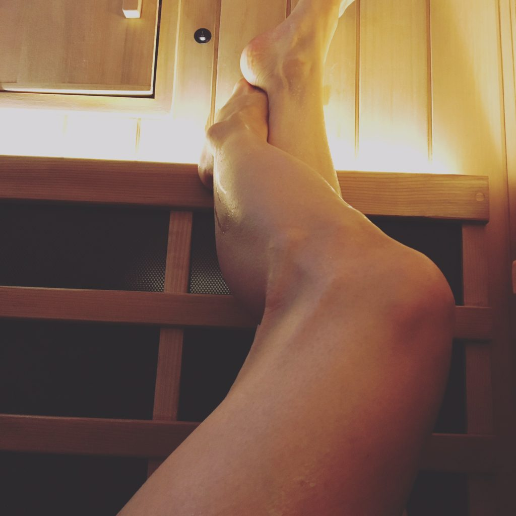 woman hanging her legs while doing infrared sauna