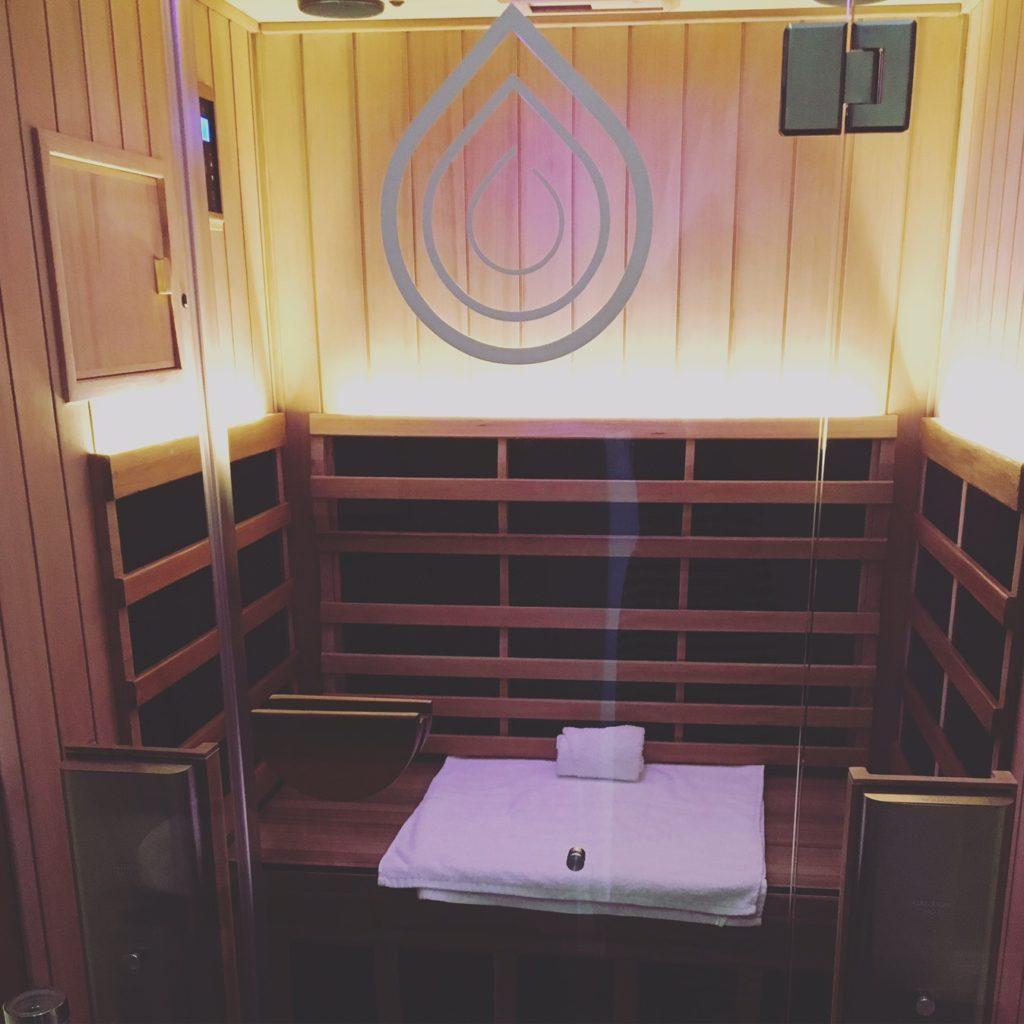 sauna room with towels and glass door